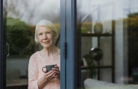 picture of senior woman at a glass window, to represent story about long-term care