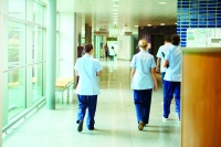 a group of four young trainee nurses including male and female nurses , walk away from camera down a hospital corridor . They are wearing uk nurse uniforms of trousers and tunics.