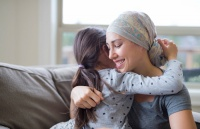 Young adult female with cancer hugging her daughter