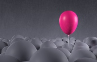 Bright purple pink party balloon emerging from a crowd of dark, gray anonymous balloons. Being special, standing out from the crowd, focusing on own individuality. Front view, looking up. Copy space on dark side of image, gray background.