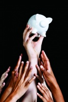 Many hands reach up to grab piggy bank one holds