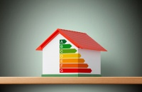 Miniature model house with energy efficiency graph.