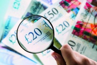 Focusing on money - Magnifying glass over British pound notes.