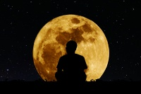 Silhouette a man sitting relaxing under full moon at night