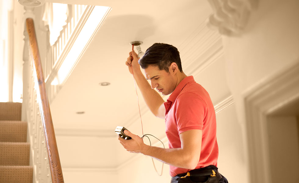 Electrician testing downlights in period home