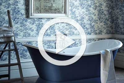 Blue freestanding bathtub with toile wallper on wall in background