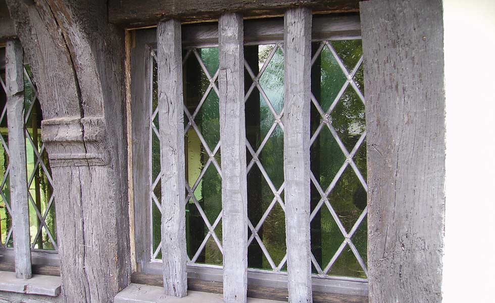 Deacon & Sandys leaded light window behind oak barred opening