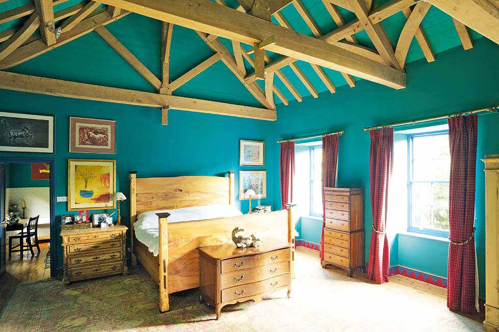 green walled master bedroom with timber beams
