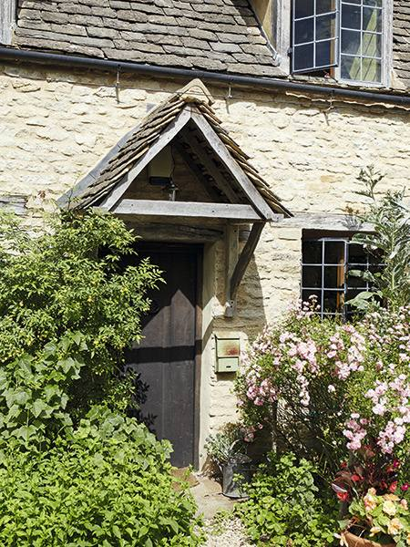 Reclaimed door on a 17th-century Cotswold stone cottage