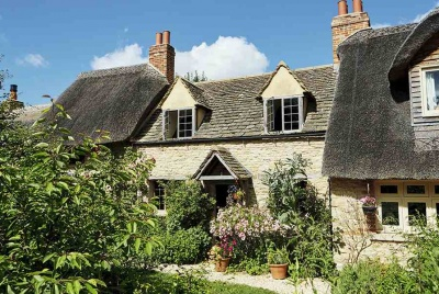Exterior of renovated 17th-century part-thatched cottage in the Cotswolds