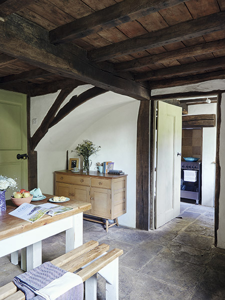 Dining room through to kitchen in renovated 17th-century cottage
