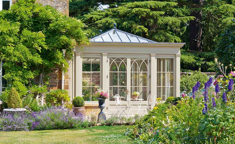 Vale Garden Houses bespoke Douglas fir orangery with an inset glazed roof, Tuscan pilasters and gothic arch detail to the doors