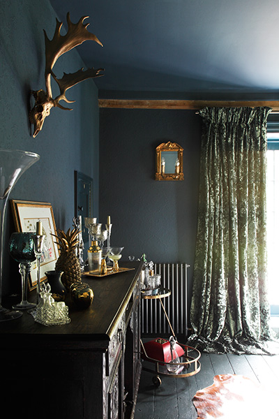 Dramatic luxe dining room with velvet curtains and drinks trolley