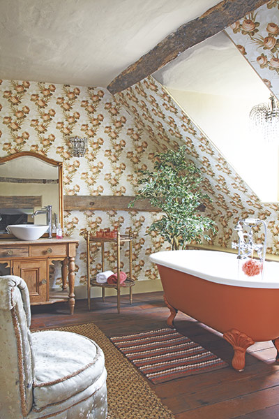 Bathroom with floral wallpaper and orange roll top bath