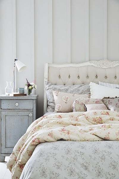 grey floral romantic bedroom with floral bedding and buttoned headboard