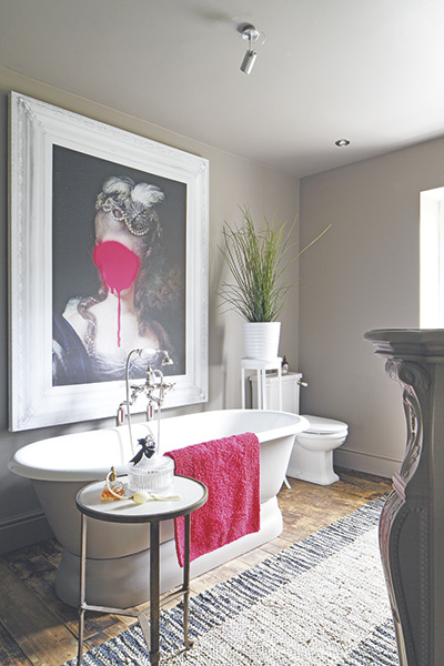 Period statement bathroom with rolltop bath and eclectic artwork