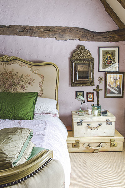 rustic feminine vintage bedroom with antique needlepoint bed