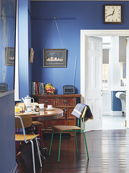 antique breakfast table with contemporary chairs in kitchen with blue walls in a Victorian home