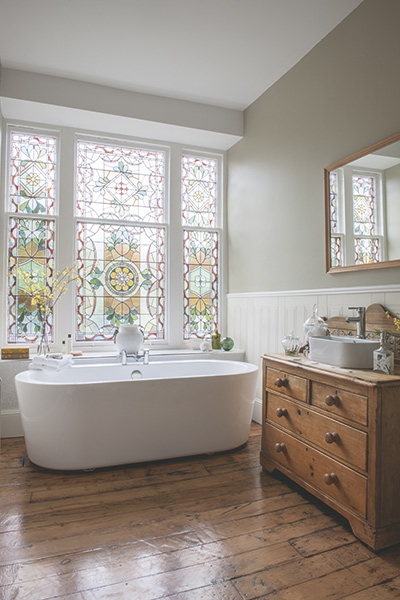 bathroom in listed georgian home with stained glass window and freestanding bath