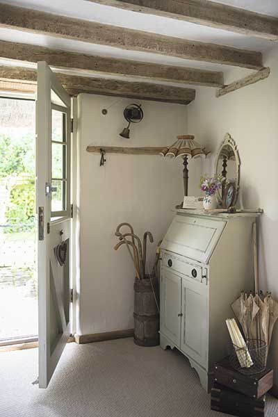 Country cottage hallway with bureau and vintage accessories