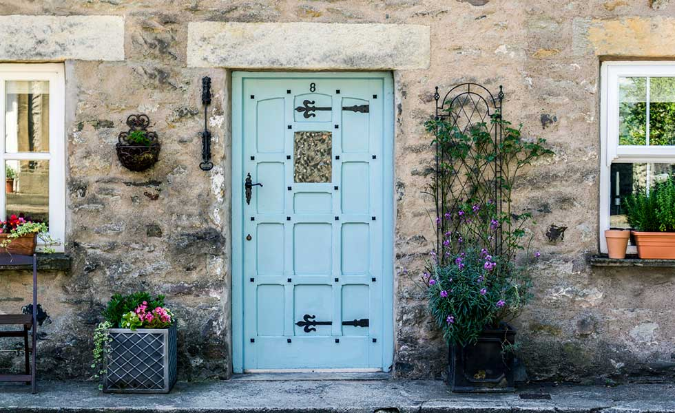 Stone cottage with blue door and authentic ironmongery