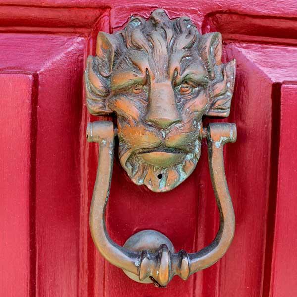 Decorative door knocker on red door