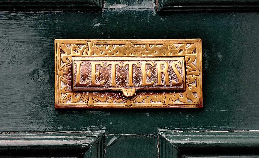 Ornate letterbox on black front door