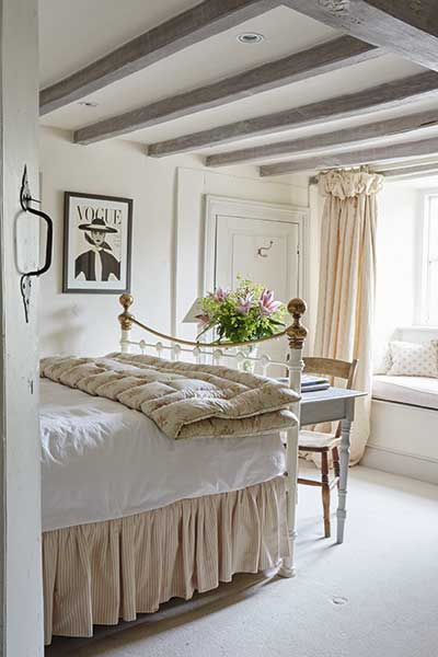bedroom with painted beams in an extended 18th-century farmhouse