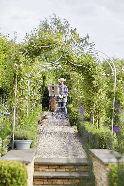 rose arbour in garden of farmhouse with lady painting