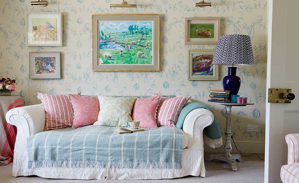 sofa with pink cushions in living room of a 18th-century farmhouse