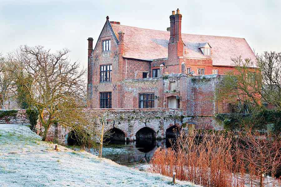 medieval red brick manor house with moat