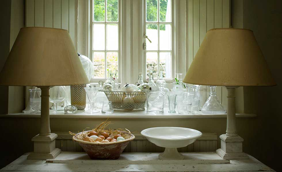 A display of glass catches the light on the kitchen windowsill