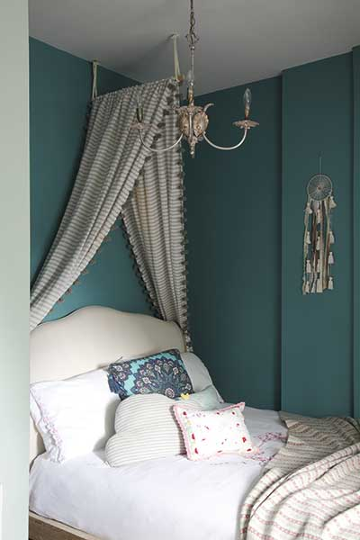 green painted bedroom with canopy and chandelier