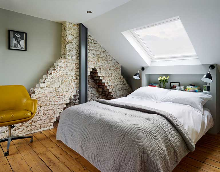 bedroom with an exposed brick wall