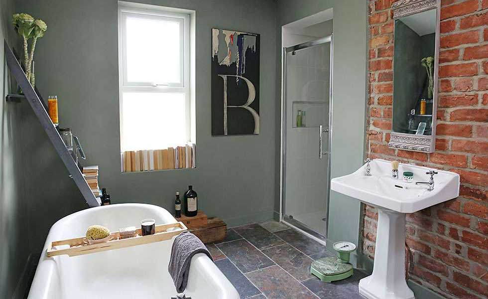 bathroom with an exposed brick wall