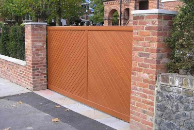 A stunning driveway gate complimenting the traditional brick pillars and building behind