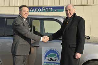 David Weir, right, director of the University of Delaware's Office of Economic Innovation and Partnerships (OEIP) shakes hands with Dick Johnson, director of business development at AutoPort. The company is the first licensee of UD's vehicle-to-grid (V2G)