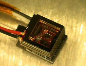 NIST's miniature magnetic sensor is about the size of a sugar cube. The lid has been removed to show the inner square cell, which contains a gas of rubidium atoms. The diagonal bar is an electrical connection to the cell's heaters, which are powered by th