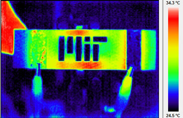 Infrared themographic image of a nanoengineered composite heated via electrical probes (clips can be seen at bottom of image). The scalebar of colours is degrees Celsius. The MIT logo has been machined into the composite, and the hot and cool spots around