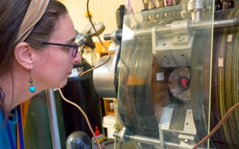 Lenore Rasmussen examines a titanium coupon used in her synthetic muscle being treated in an oxygen plasma at PPPL