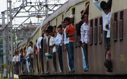 Passengers ride on the side of commuter train in Mumbai, India