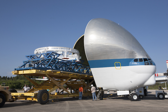 The Orion spacecraft service module stacking assembly interface ring and stack holding stand are secured on a special transportation platform and are being loaded into NASA's Super Guppy aircraft at the Shuttle Landing Facility at NASA's Kennedy Space Cen