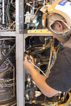 Aviation Mechanic Cody Schwarz works to install a 3D printed, titanium link and fitting on an MV-22 Osprey engine nacelle