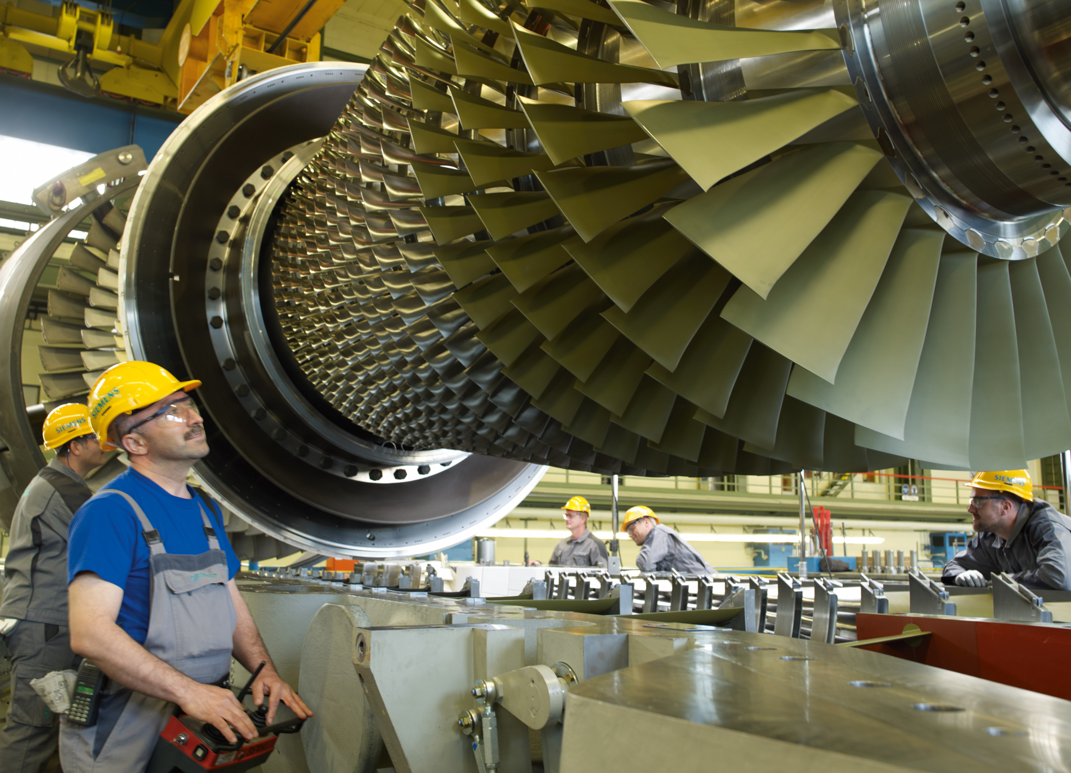 Das Bild zeigt Siemens-Mitarbeiter in der Endmontage beim Einlegen eines Turbinenläufers der Siemens Gasturbine SGT5-4000F. The picture shows Siemens employees in the final assembly hall in the Berlin manufacturing plant while inserting a turbine rotor of the Siemens gas turbine SGT5-4000F.