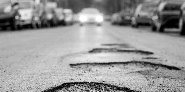Broken asphalt resulting in a pothole, dangerous to motorists. Selective focus, low-angle view