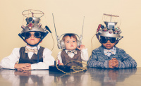A young boy imagines reading minds of his two friends with a homemade science project. They are dressed in casual clothing, glasses and bow ties. They are serious and sitting at a table with helmets on their heads in front of a beige background. To illustrate article about average IQ of lawyers