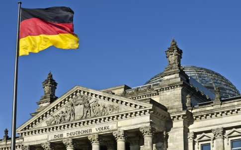 German national flag flying in front of the entrance to the Reichstag (federal parliament) building, Berlin, Germany