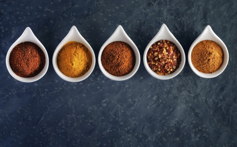 Different spices in tasting spoons on dark slate from above