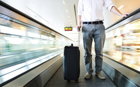 Business traveler with a suitcase at the speedwalk