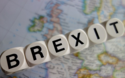 scrabble game letter panels spelling Brexit over map of UK and mainland Europe